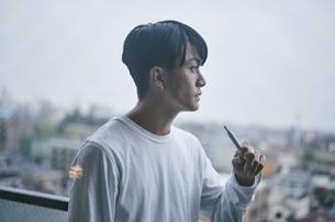 ベランダでタバコを吸う男性の写真素材 [FYI04785412]