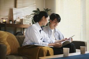 家内で本を読む男女の写真素材 [FYI04785492]