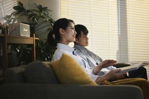 家内でテレビを見てくつろぐ男女の写真素材 [FYI04785505]