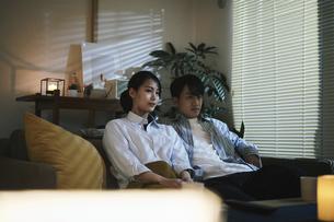 家内でテレビを見てくつろぐ男女の写真素材 [FYI04786132]