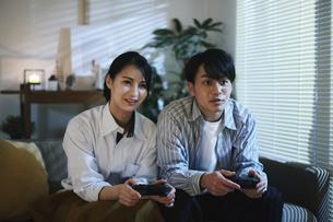 家内でゲームをする男女の写真素材 [FYI04786139]