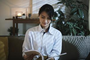 家内で本を読む女性の写真素材 [FYI04786149]