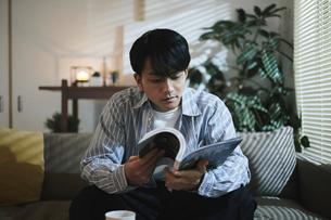 家内で本を読む男性の写真素材 [FYI04786173]