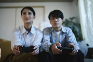 家内でゲームをする男女の写真素材 [FYI04786177]