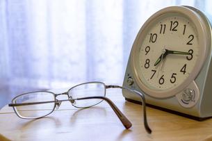 窓際の置き時計とめがねの写真素材 [FYI04787540]