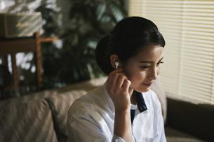 イヤホンをして音楽を聞く女性の写真素材 [FYI04787853]