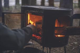 冬のキャンプ。野外で薪ストーブのアウトドア料理。の写真素材 [FYI04788664]