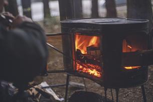 冬のキャンプ、薪ストーブに火吹き棒で火力を上げるの写真素材 [FYI04788667]