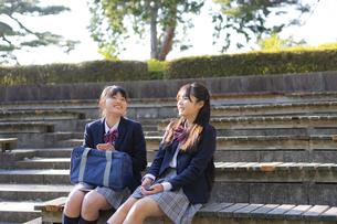 公園でくつろぐ女子学生2人の写真素材 [FYI04788921]