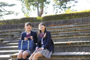 公園でくつろぐ女子学生2人の写真素材 [FYI04788922]