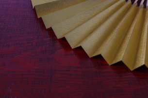 漆塗り板背景の金色の扇子の写真素材 [FYI04789275]