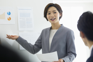 ホワイトボード前でプレゼンをする女性の写真素材 [FYI04789343]