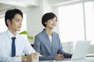 隣り合わせで座るビジネス男女の写真素材 [FYI04789350]