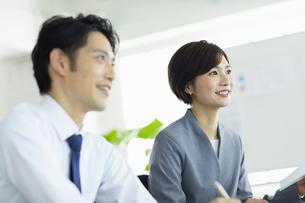 隣り合わせで座るビジネス男女の写真素材 [FYI04789351]