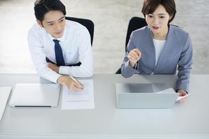 隣り合わせで座るビジネス男女の写真素材 [FYI04789353]
