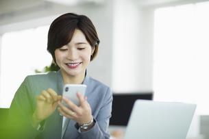 デスクで笑顔でスマーフォンを操作する女性の写真素材 [FYI04789358]