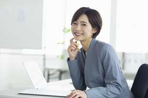 ビジネスオフィスで笑顔の女性の写真素材 [FYI04789359]