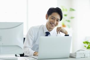 ビジネスオフィスでパソコンに向き合う男性の写真素材 [FYI04789367]