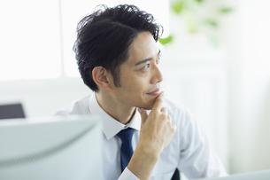 ビジネスオフィスで窓の外を見る男性の写真素材 [FYI04789368]