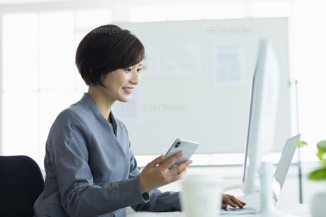 デスクで笑顔でスマーフォンを操作する女性の写真素材 [FYI04789369]
