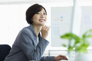 デスクで笑顔で仕事をする女性の写真素材 [FYI04789372]