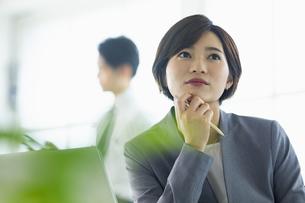 デスクで考え事をする女性の写真素材 [FYI04789373]
