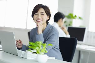 デスクで笑顔の女性の写真素材 [FYI04789376]