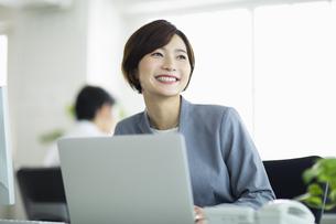 デスクで笑顔の女性の写真素材 [FYI04789378]