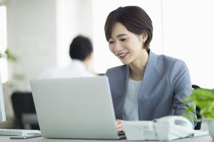 デスクで仕事をする女性の写真素材 [FYI04789379]