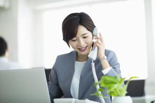 デスクで電話対応をする女性の写真素材 [FYI04789380]