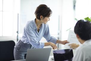 同僚に資料を渡す女性の写真素材 [FYI04789398]