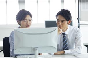 パソコンを一緒に見る男女の写真素材 [FYI04789408]