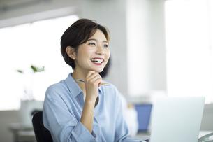 デスクで笑顔で仕事をする女性の写真素材 [FYI04789418]