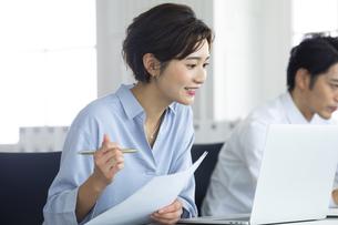 デスクで笑顔で仕事をする女性の写真素材 [FYI04789419]