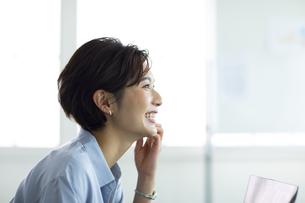 デスクで笑顔で仕事をする女性の写真素材 [FYI04789426]