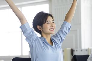 デスクで笑顔で伸びをする女性の写真素材 [FYI04789427]