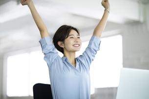 デスクで笑顔で伸びをする女性の写真素材 [FYI04789436]