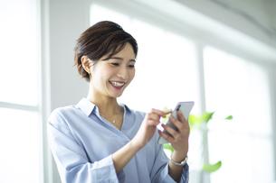 窓際でスマートフォンを操作する女性の写真素材 [FYI04789437]