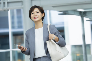 スマートフォンを持ったビジネススーツの女性の写真素材 [FYI04789467]