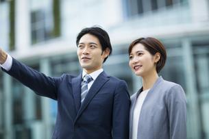 横に並び指を指すビジネススーツの男女の写真素材 [FYI04789496]