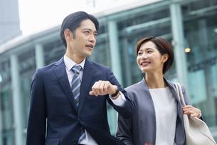 会話しながら歩くビジネススーツの男女の写真素材 [FYI04789505]