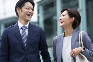 会話しながら歩くビジネススーツの男女の写真素材 [FYI04789506]