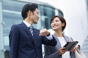 会話しながら歩くビジネススーツの男女の写真素材 [FYI04789515]