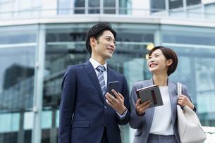 会話しながら歩くビジネススーツの男女の写真素材 [FYI04789516]