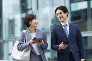 会話しながら歩くビジネススーツの男女の写真素材 [FYI04789517]
