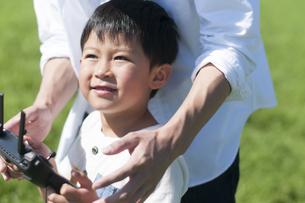 草原でドローンを操縦する親子の写真素材 [FYI04789518]