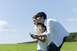 草原でドローンを操縦するファミリーの写真素材 [FYI04789522]