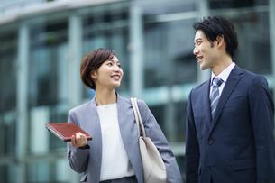 会話しながら歩くビジネススーツの男女の写真素材 [FYI04789525]