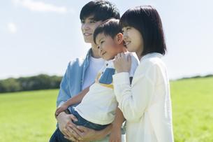 草原で子供を抱くファミリーの写真素材 [FYI04789541]