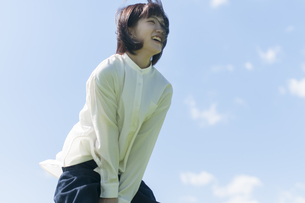 草原で風に吹かれる女性の写真素材 [FYI04789544]